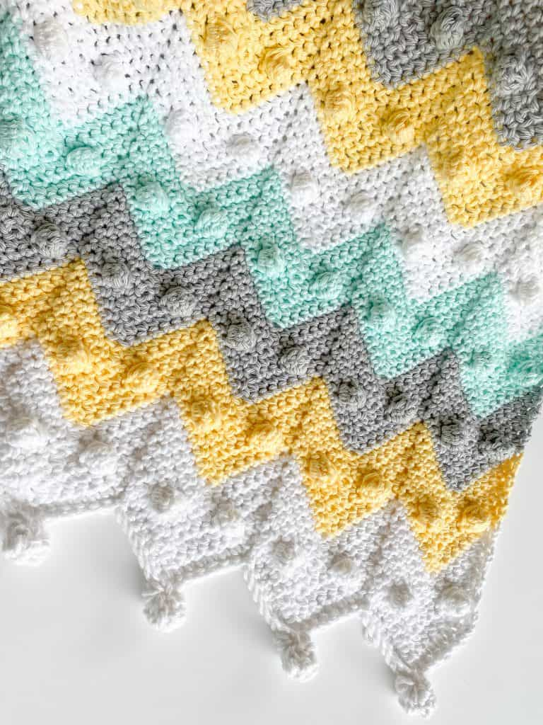 Beginner-friendly bobble chevron baby blanket crochet pattern makes the perfect baby shower gift! With my easy-to-follow video tutorial, you'll have your blanket done in no time! Stroller-sized newborn blanket with instructions to make in any size. Using I Love this Cotton yarn from Hobby Lobby.